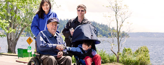 Photo: Family with disabled child and parent walking outdoors