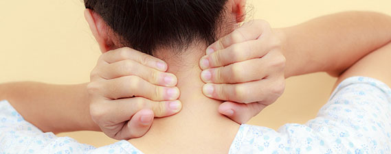 Photo: Woman holding her sore neck